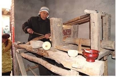 艺人在古老的木旋床上切